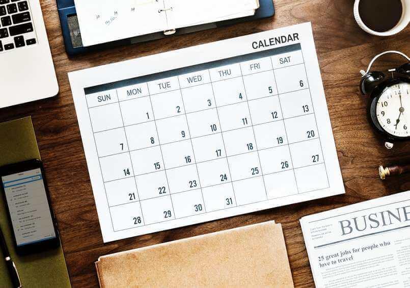 calandar laptop clock phone and business newspaper on desk