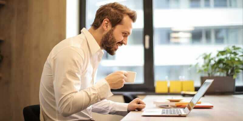 man-holding-teacup-infront-of-laptop-on-top-of-table-inside